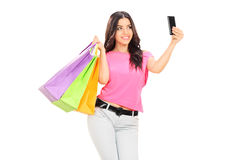 Beautiful girl holding shopping bags and taking selfie. With cell phone isolated on white background royalty free stock photos