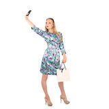 Beautiful girl holding shopping bags and taking selfie with cell phone isolated. On white background royalty free stock photos