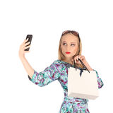 Beautiful girl holding shopping bags and taking selfie with cell phone isolated Royalty Free Stock Images