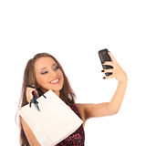 Beautiful girl holding shopping bags and taking selfie with cell phone Stock Photos