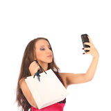 Beautiful girl holding shopping bags and taking selfie with cell phone Stock Photography