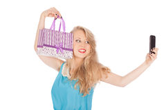 Beautiful girl holding shopping bags and taking selfie with cell phone Royalty Free Stock Photo