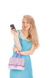 Beautiful girl holding shopping bags and taking selfie with cell phone Royalty Free Stock Images