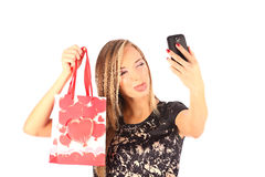Beautiful girl holding shopping bags and taking selfie with cell phone isolated Stock Image