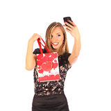Beautiful girl holding shopping bags and taking selfie with cell phone isolated Stock Photography