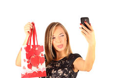 Beautiful girl holding shopping bags and taking selfie with cell phone isolated Stock Images