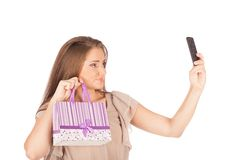 Beautiful girl holding shopping bags and taking selfie with cell phone isolated Royalty Free Stock Photography