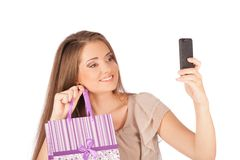 Beautiful girl holding shopping bags and taking selfie with cell phone isolated Royalty Free Stock Photo