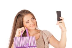 Beautiful girl holding shopping bags and taking selfie with cell phone isolated Stock Photos