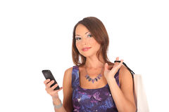 Beautiful girl holding shopping bags and taking selfie with cell phone isolated on white Stock Images