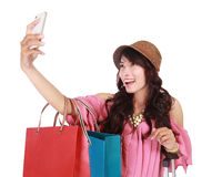 Beautiful girl holding shopping bags and taking selfie. With cell phone, isolated on white background Stock Images