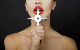 Beautiful girl holding a shuriken. Shuriken in a hand on a black background, sexy lips and shuriken Royalty Free Stock Images