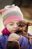 Beautiful girl holding small chihuahua dog, friendship concept Stock Photos
