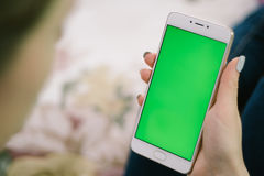 Beautiful girl holding a smartphone in the hands of a green scre Stock Images