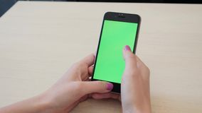 Beautiful girl holding a smartphone in the hands of a green screen green screen, hand of man holding mobile smart phone. Beautiful girl holding a smartphone in stock video