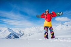 beautiful girl is holding a snowboard board on her shoulder. Smiling stock images