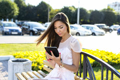 Beautiful girl holding  tablet, bright sunny day, on a bench, fashion style urban life. Read e-books, sitting social Royalty Free Stock Images