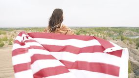 Beautiful girl holding a waving American flag in nature. Independence Day, lifestyle, travel concept.  stock footage