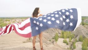 Beautiful girl holding a waving American flag in nature. Independence Day, lifestyle, travel concept.  stock video footage
