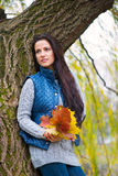 Beautiful girl holding yellow autumn leaves Royalty Free Stock Photo