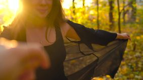 Beautiful girl holds the hand of her boyfriend and follows him through the yellow autumn forest. Weekend outside the city stock video