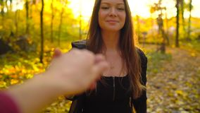 Beautiful girl holds the hand of her boyfriend and follows him through the yellow autumn forest. Weekend outside the city stock footage