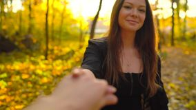 Beautiful girl holds the hand of her boyfriend and follows him through the yellow autumn forest. Slow motion. Beautiful girl holds the hand of her boyfriend and stock video footage