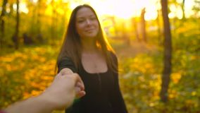 Beautiful girl holds the hand of her boyfriend and follows him through the yellow autumn forest. Slow motion. Beautiful girl holds the hand of her boyfriend and stock footage
