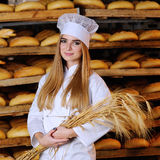 Beautiful girl holds in hands ears of wheat. Pretty blonde girl holds in hands ears of wheat on background bakery Stock Photography
