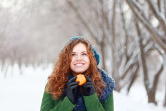 Beautiful girl holds mandarin and looks up at wint Royalty Free Stock Images