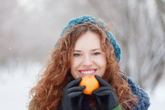 Beautiful girl holds mandarin and smiles outdoor. Beautiful girl in blue beret holds mandarin and smiles outdoor at winter day in park royalty free stock photos