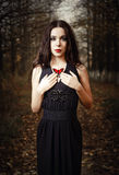 Beautiful girl holds red butterfly in hands. Outdoor portrait Stock Image
