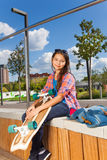Beautiful girl holds skateboard and sits on side Stock Photo
