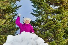 Beautiful girl holds snowball behind snow wall Stock Images