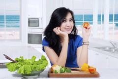 Beautiful girl holds tomato in kitchen Royalty Free Stock Photo