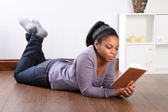 Beautiful girl at home on the floor reading a book Royalty Free Stock Images