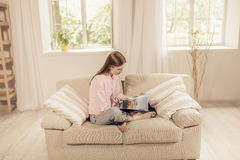 Beautiful girl at home sitting on the couch, reading a magazine. Stock Images
