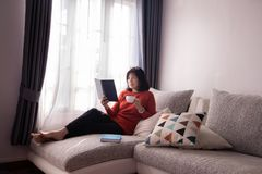 Beautiful girl at home sitting on the couch, reading a magazine and having a coffee break stock photos