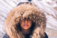 Beautiful girl in a hood with fur of a winter jacket. The girl`s face is hidden in a hood with fur. Royalty Free Stock Images