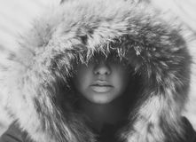 Beautiful girl in a hood with fur of a winter jacket. The girl`s face is hidden in a hood with fur. Stock Photo