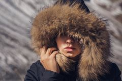 Beautiful girl in a hood with fur of a winter jacket. The girl`s face is hidden in a hood with fur. Royalty Free Stock Photo