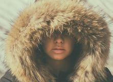 Beautiful girl in a hood with fur of a winter jacket. The girl`s face is hidden in a hood with fur. Royalty Free Stock Photography
