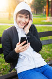 Beautiful girl with a hood sitting in the park and listening to music Stock Photography