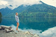 Beautiful Girl in a hoodie. Mountain blue lake green. Beautiful Girl in a hoodie. Mountain blue lake green Royalty Free Stock Photos