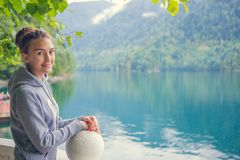 Beautiful Girl in a hoodie. Mountain blue lake green. Beautiful Girl in a hoodie. Mountain blue lake green Royalty Free Stock Photography