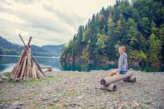 Beautiful Girl in a hoodie. Mountain blue lake green. The fire. Beautiful Girl in a hoodie. Mountain blue lake greenBeautiful Girl in a hoodie. Mountain blue Royalty Free Stock Image
