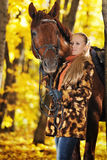 Beautiful girl with horse in autumn forest Stock Photography