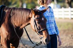 Beautiful girl with horse. Beautiful girl leading her brown horse at the farm Stock Photo