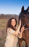 Beautiful girl with a horse outdoors. Beautiful girl with a horse outdoors in the countryside Royalty Free Stock Image