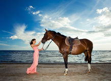 Beautiful girl  with horse on seacoast Royalty Free Stock Images